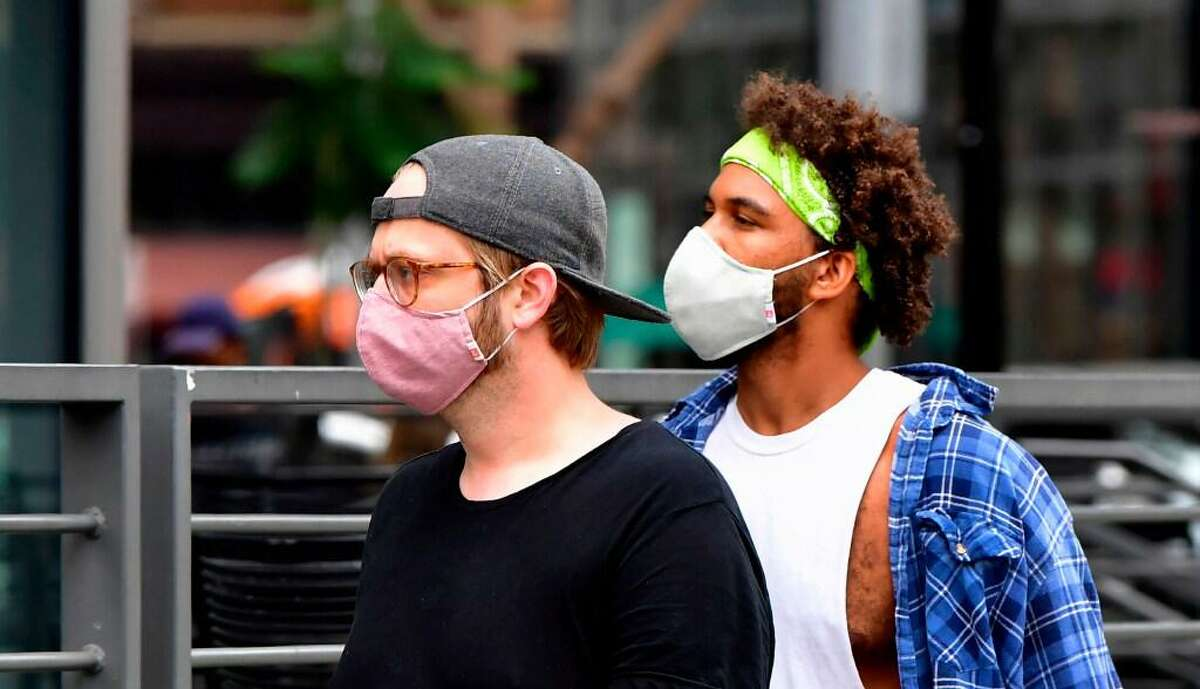 Young men wear face masks last month in Los Angeles.