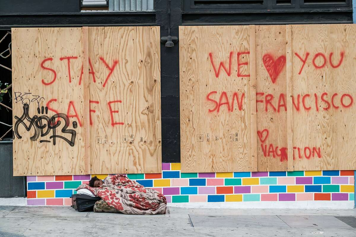 A homeless man sleeps near a boarded up store front in San Francisco, Calif. on Monday, March 23, 2020.
