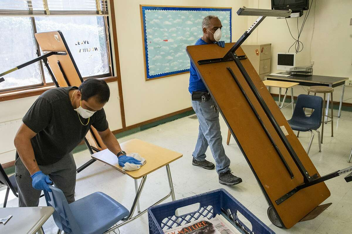 From left: Custodians Orlando Lavarias and Herman Flood clean and sanitize a classroom that will be set up for physical distancing at Westlake Middle School on Friday, July 10, 2020, in Oakland, Calif.