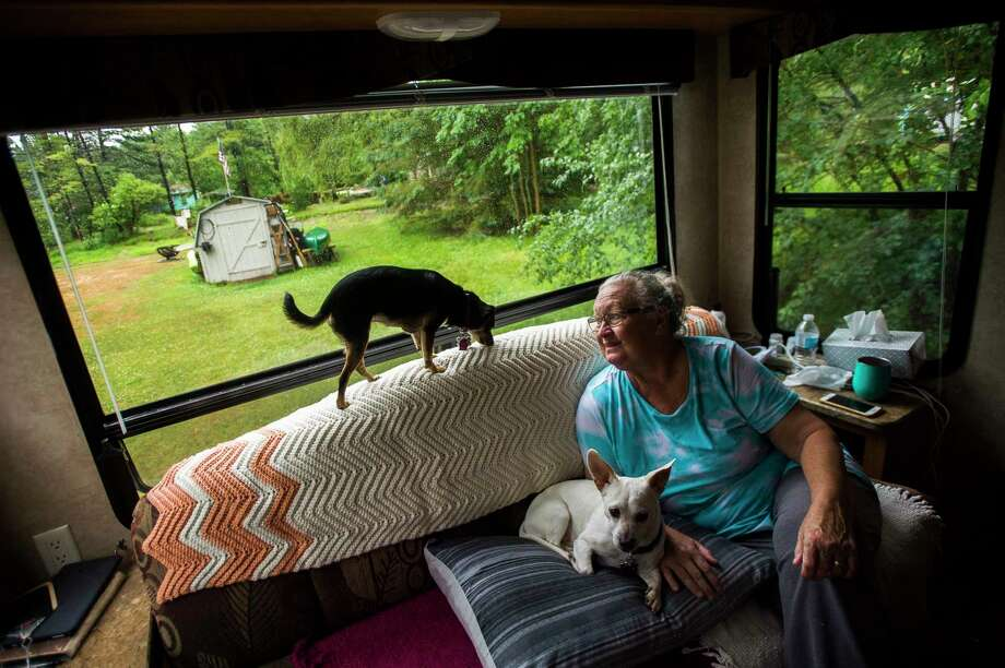 Cindy Matthias relaxes with her two dogs, Lily and Frankie, Friday morning inside the RV she and her husband Brian are sleeping in asthey finish renovating their home on Ostlund Drive in Hope, which was severely damaged in May's flood. (Katy Kildee/kkildee@mdn.net)