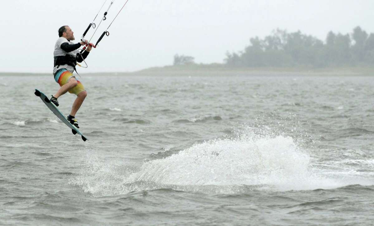 Wind and kite surfers take to the waters off Calf Pasture Beach to take advantage of the high winds brought by a tropical storm on Friday in Norwalk.