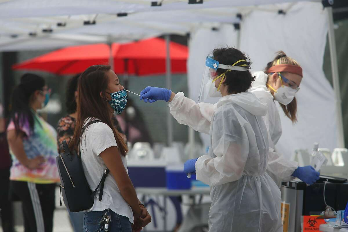 Ann Chan (right), physicians assistant with Carbon, conducts a COVID-19 test at the COVID-19 testing site at the Native American Health Center on Thursday, July 9, 2020 in Oakland, Calif.