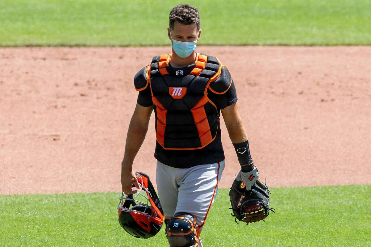 San Francisco Giants catcher Buster Posey wears a mask while taking his position behind home base during the San Francisco Giants' summer training camp session at Oracle Park in San Francisco, Calif. Saturday, July 4, 2020. Due to COVID-19, the 2020 MLB season has been postponed with players just beginning to return for warmups and practices while wearing masks and keeping social distance.