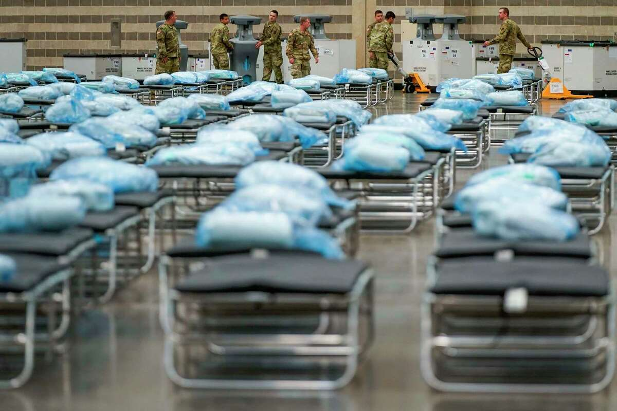 Texas Army National Guardsmen unpack crates of supplies as they set up a field hospital in response to the new coronavirus crisis at the Kay Bailey Hutchison Convention Center on Tuesday, March 31, 2020, in Dallas. (Smiley N. Pool/The Dallas Morning News/Pool)