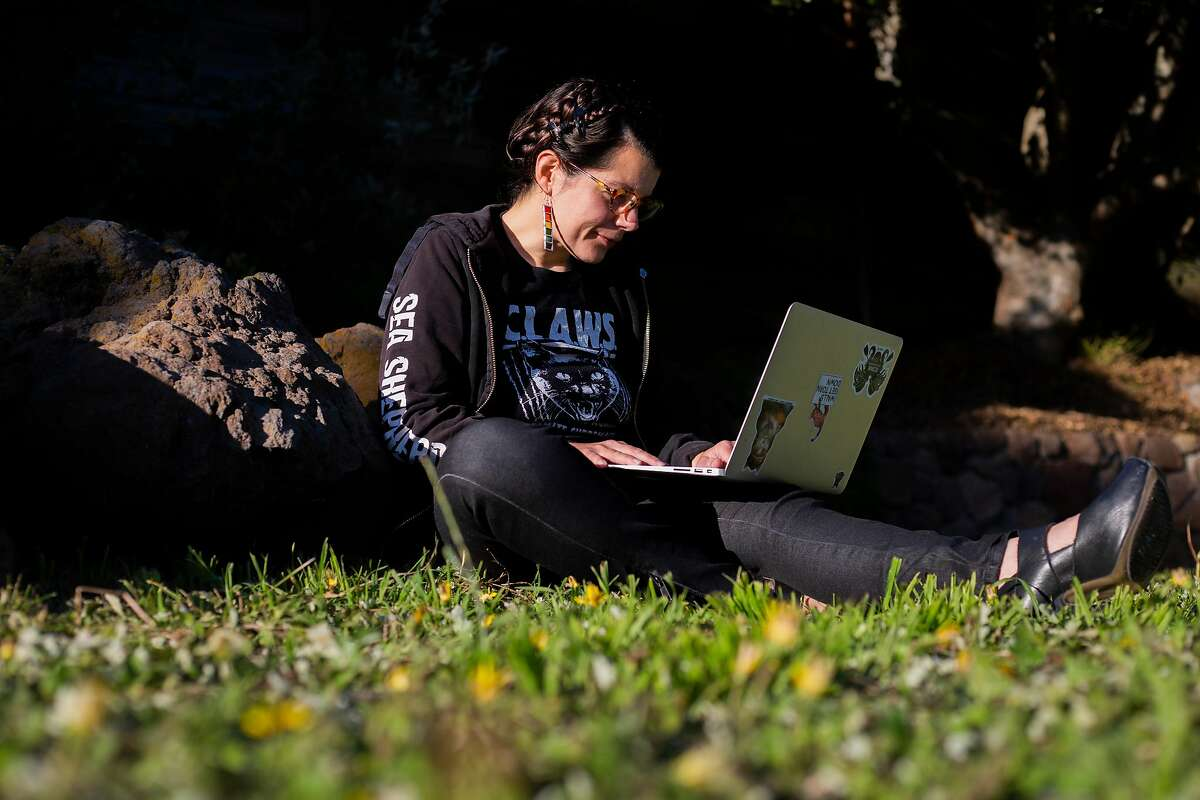 Jennifer Moless, sits on her computer outside her apartment complex in Portola in San Francisco, CA on July 9, 2020.