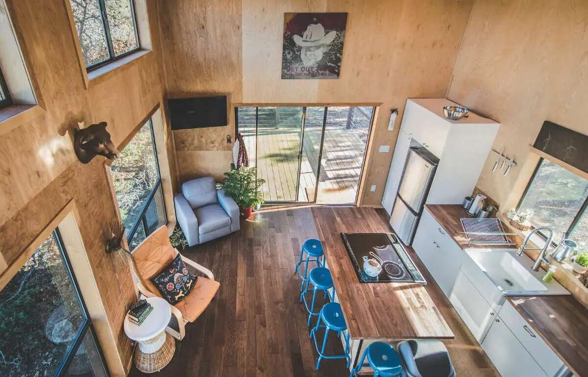 This farmhouse-modern guest cabin rests upon a hill with big windows opening up to creekside views of the Wanderin' Star Farms.