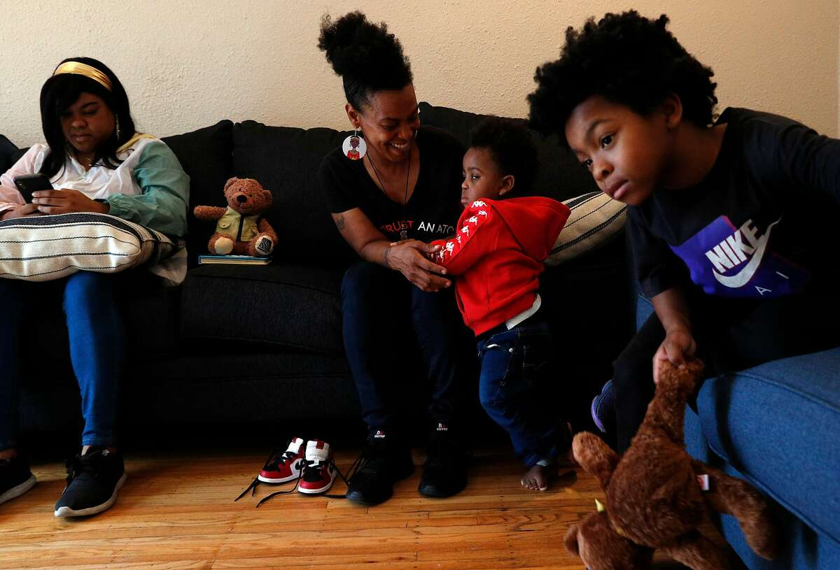 Sabrina Hall plays with her grandson August, 14 mos, center, and son, Brandon, 7, right, and daughter, Brittany, left, in her home where she is riding out the shelter in place and hoping to get back to work in San Francisco, Calif., on Monday, June 29, 2020. Hall lives in the Bayview with her four children and grandchild. She was forced to leave her job as an SFO ramp operator in late February and then again in March to get tested for the coronavirus. Although she came back negative twice, she lost out on about two weeks of pay because testing wasn't more readily available in her community.