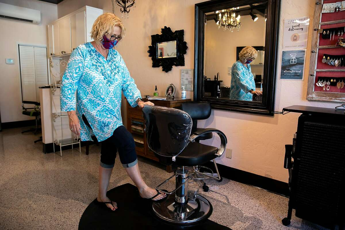 Fabu salon owner Mary Hill sets her chair height as she prepares to open her salon on Friday, July 10, 2020 in Campbell, Calif. Hill is preparing to open the salon to the public after agreeing to protocols and restrictions placed by the county.