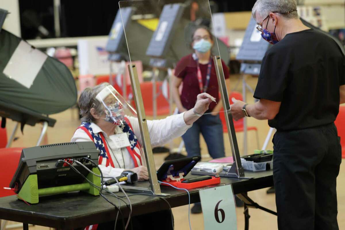 Kathy Kellen sits behind and wears a plastic shield and face covering as she helps an early voter at the Metropolitan Multi-Services Center, 1475 W Gray St., Monday, June 29, 2020, in Houston.