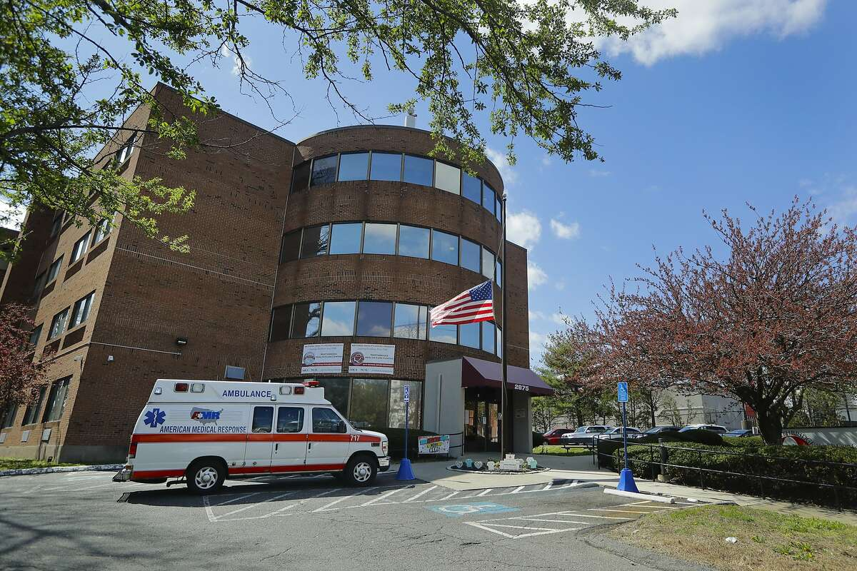 An ambulance used to transport a patient is parked outside the Northbridge Health Care Center Wednesday, April 22, 2020, in Bridgeport, Conn.