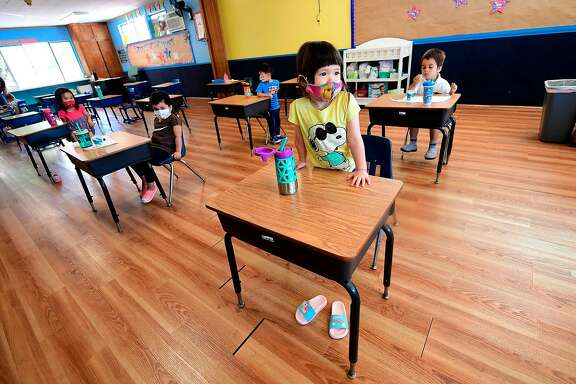 Children in a pre-school class wear masks and sit at desks spaced apart as per coronavirus guidelines during summer school sessions at Happy Day School in Monterey Park, California on July 9, 2020. - California Governor Gavin Newsom says the reopening of California schools for the coming school year will be based on safety and not pressure from President Donald Trump as California sets records for one-day increases in COVID-19 cases. (Photo by Frederic J. BROWN / AFP) (Photo by FREDERIC J. BROWN/AFP via Getty Images)