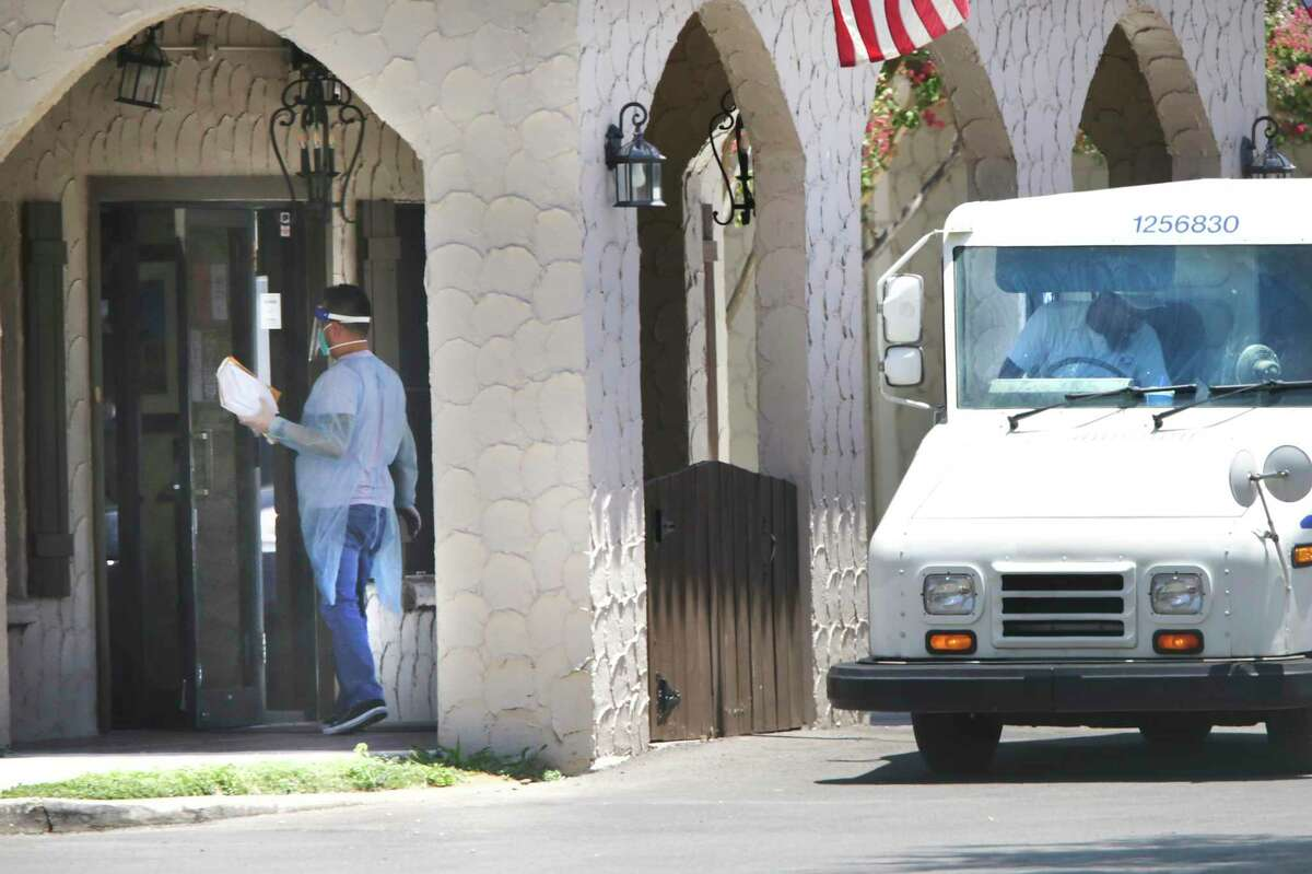 An employee at Windsor Mission Oaks, left, wears personal protective equipment as he picked up the mail from an unmasked postal worker on Friday, July 10, 2020. Testing conducted at Windsor Mission Oaks has found positive COVID-19 cases among staff and residents.