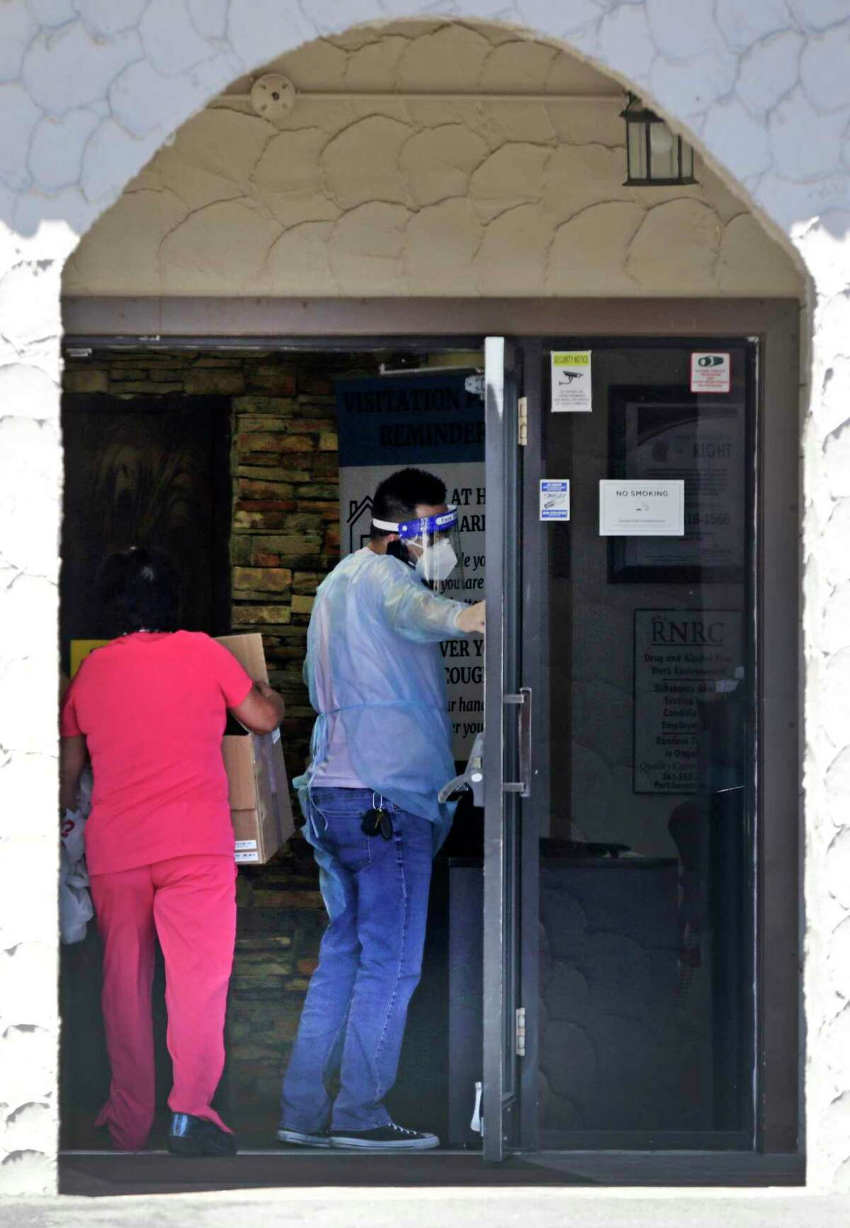 A worker wearing personal protective equipment holds the door for a caretaker bringing supplies to Windsor Mission Oaks nursing home on Friday, July, 10, 2020.