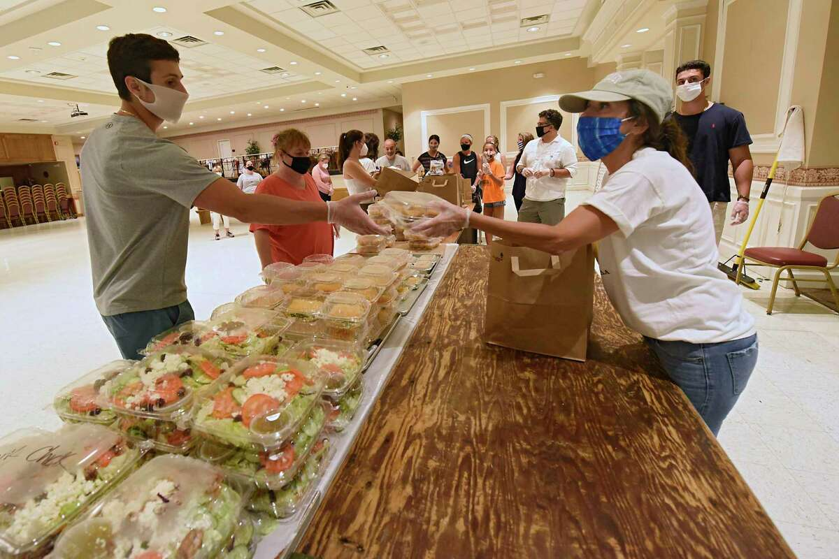 Volunteers gather and deliver orders to people in a drive-through manner during what would have been the 50th annual Greek Festival at St. Sophia Greek Orthodox Church on Friday July 10, 2020 in Albany, N.Y. Because of the COVID-19 pandemic, food must be ordered online and picked up at the drive-thru in the church parking lot. (Lori Van Buren/Times Union)