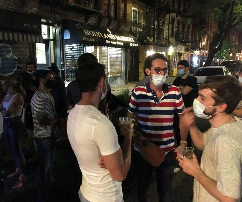 Scenes in New York City in the summer of 2020 as the coronavirus crisis subsides reveal a mix of distancing and crowding, mask-wearing and none. Shown are partiers dancing at a late-night, spontaneous gathering in SoHo; doctors at a bar in the East Village; two runners at the Metropolitan Museum of Art; and a night scene on Broadway. Photo: Dan Haar/Hearst Connecticut Media
