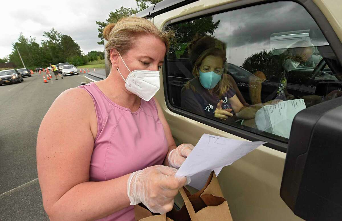 Volunteer Kella Papa, left, goes over an order as she delivers food to people in a drive-through manner during what would have been the 50th annual Greek Festival at St. Sophia Greek Orthodox Church on Friday July 10, 2020 in Albany, N.Y. Because of the COVID-19 pandemic, food must be ordered online and picked up at the drive-thru in the church parking lot. (Lori Van Buren/Times Union)