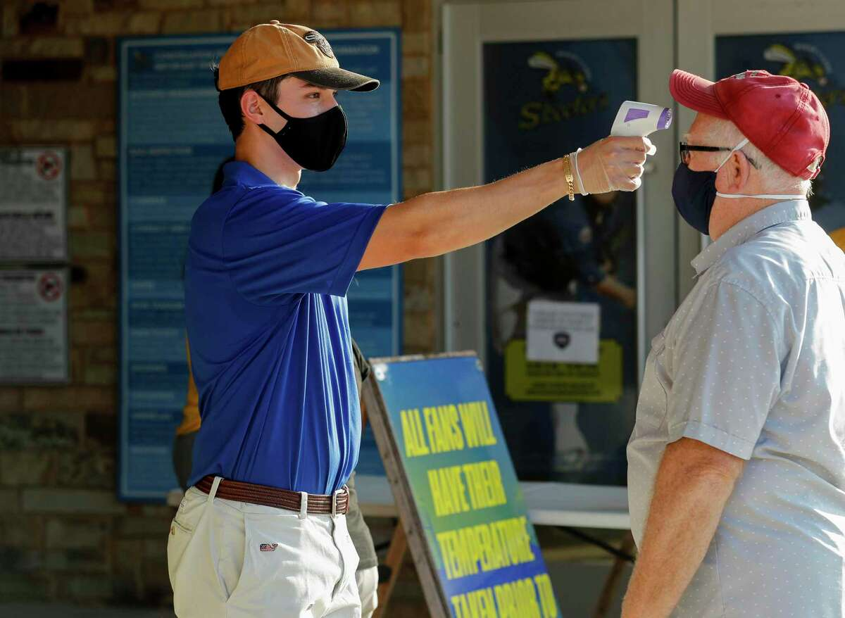 A man has his temperature checked by Skeeters staff before entering Constellation Field on Friday, July 10, 2020, in Sugar Land, Texas.