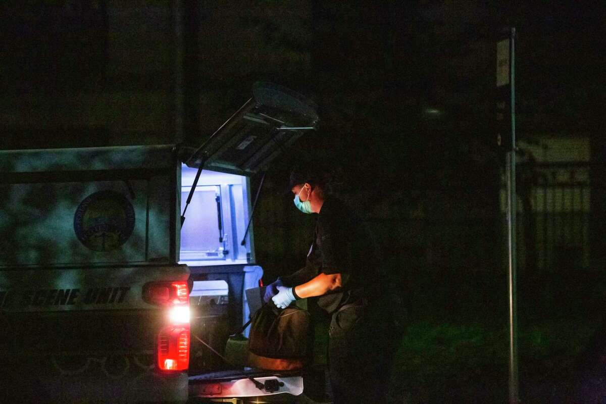 A member of the Houston Forensic Science Center works on the back of one the center's vehicle unit near the scene where two females were found dead at Camden Greenway Apartments on Friday, July 10, 2020, in Houston.