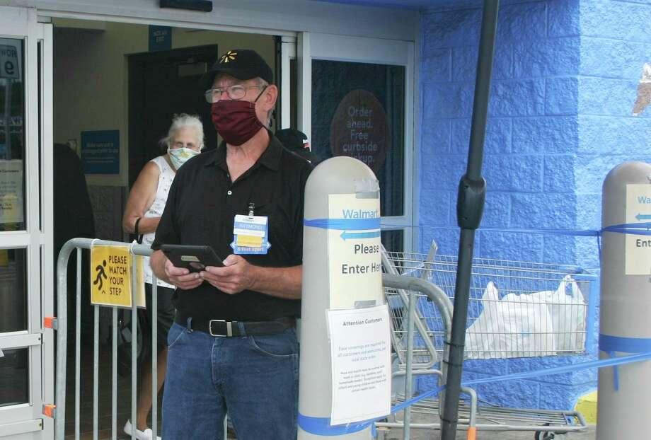 Walmart Health Ambassador Raymond Haightinforms customers of the new face mask regulations Friday outside the front entrance to the Walmart in Big Rapids. (Pioneer photo/Cathie Crew)