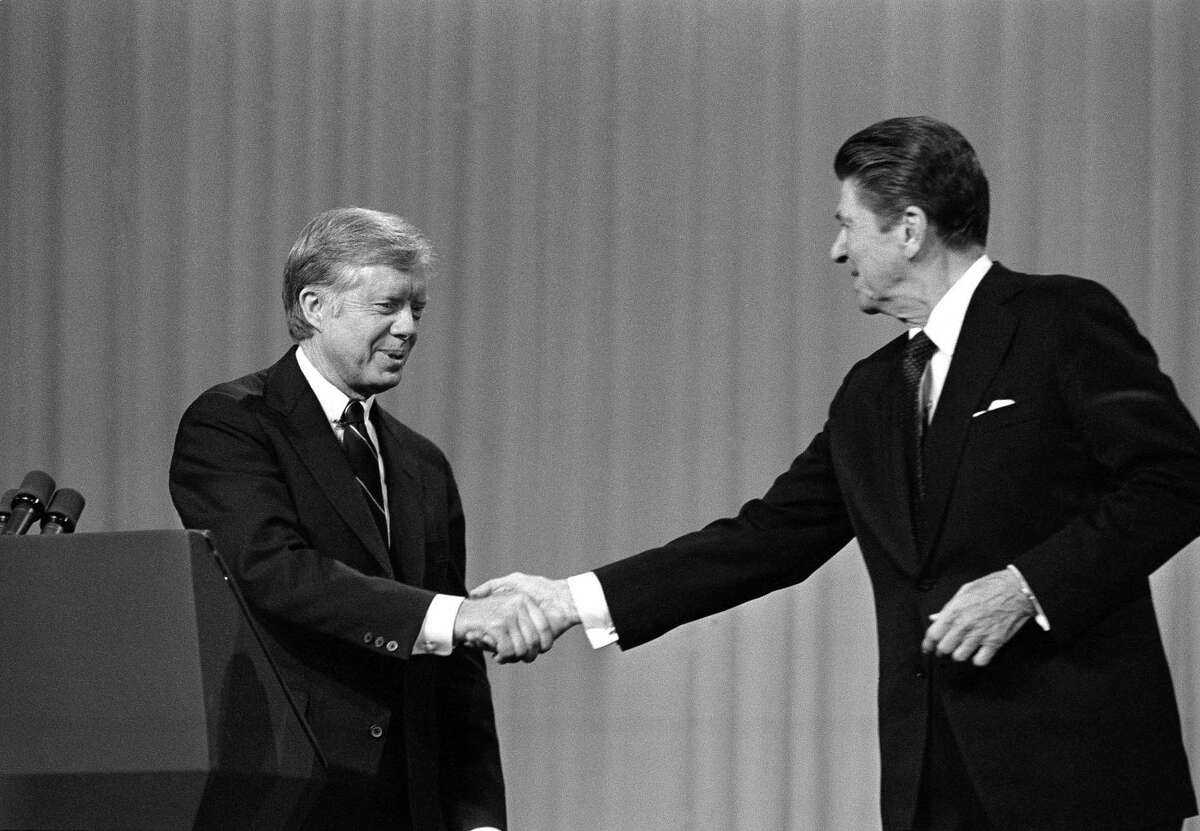 In this Oct. 28, 1980 file photo, President Jimmy Carter shakes hands with Republican Presidential candidate Ronald Reagan after debating in the Cleveland Music Hall in Cleveland.