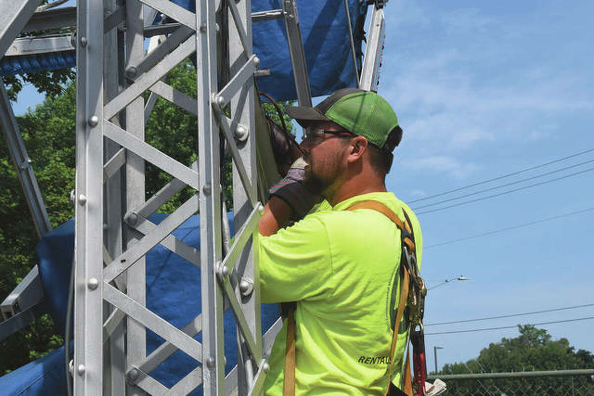 Beau Decker of Briem Engineering checks the ferris wheel in Community Park for cracks as part of an inspection.