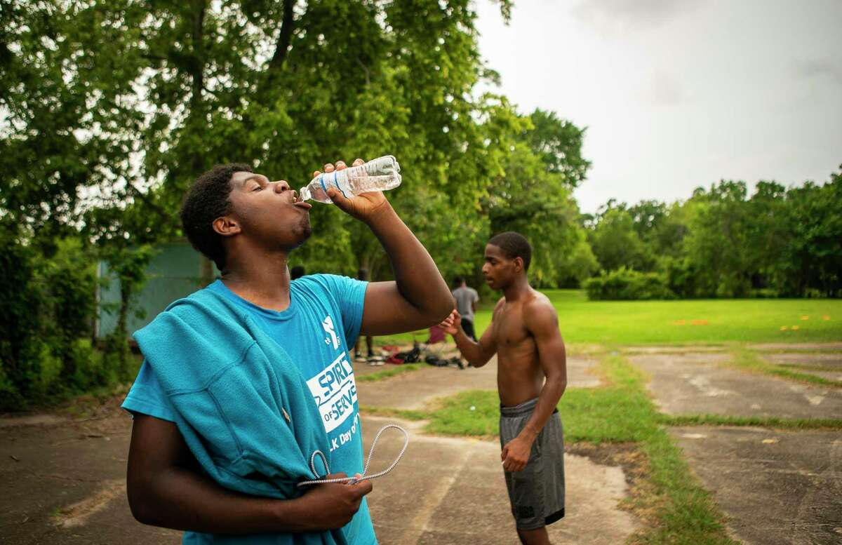 Ramadan Ahmad, who will be a senior at Yates High School this coming fall, takes a drink from a water bottle in the peak of afternoon's heat after running football drills with several classmates in an empty lot on Tuesday, July 7, 2020, in the Third Ward neighborhood of Houston. Climate scientists project more days of 100-degree heat due to climate change over the coming decades.