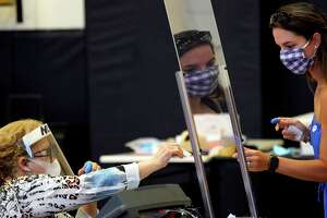 Harris County election clerk Nora Martinez, left, helps a voter, Monday, June 29, 2020, in Houston. Early voting for the Texas primary runoffs began Monday. (AP Photo/David J. Phillip)