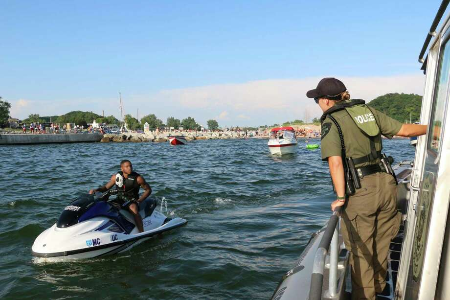 Conservation Officer Jackie Miskovich talks to someone operating a personal watercraft in Lake Michigan offshore from Grand Haven State Park in July 2019. (Courtesy photo/Michigan DNR)