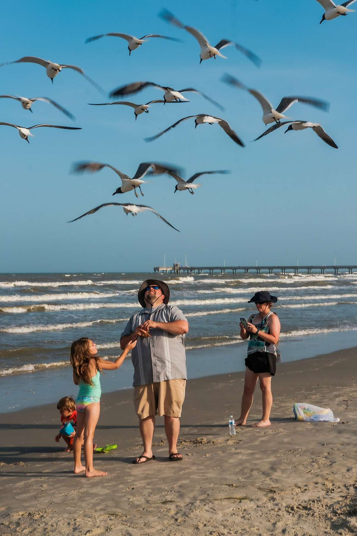 The Thornton family, visitors from Missouri, on the beach in Corpus Christi, Texas, July 7, 2020. Corpus Christi was largely spared in the early weeks of the pandemic; now the longtime south Texas beach destination has one of the fastest-growing outbreaks in the state, one driven largely by out-of-town visitors. (Christopher Lee/The New York Times)