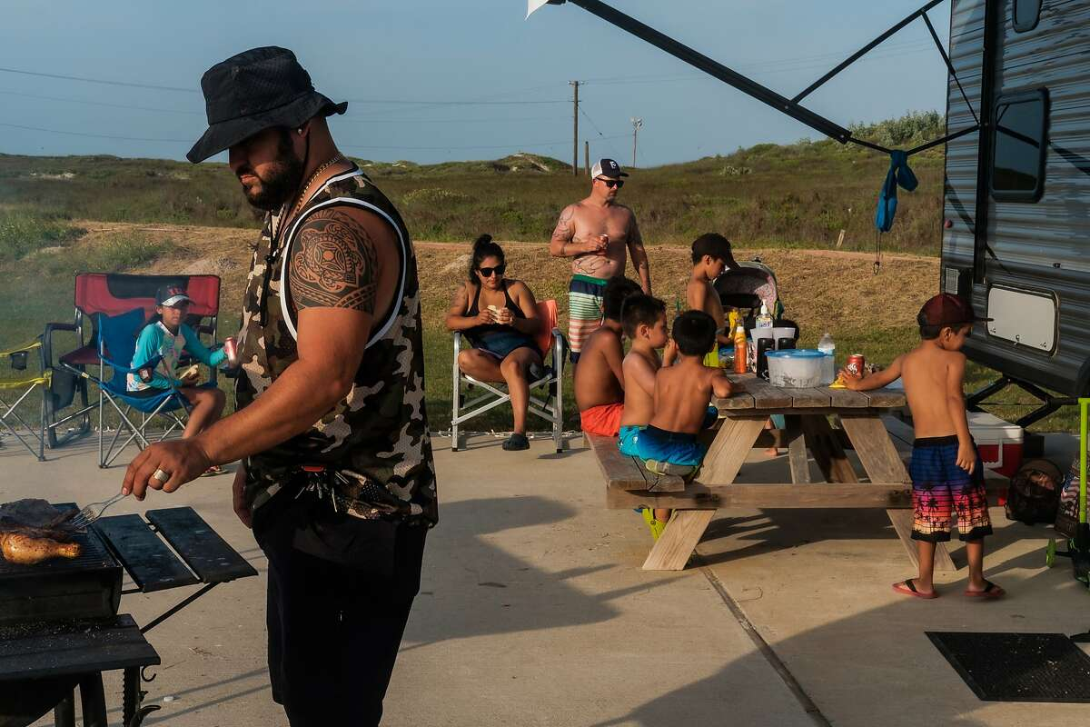 Billy Arocha of Floresville, Texas and his family grill food at an RV campsite near the beach in Corpus Christi, July 7, 2020. Corpus Christi was largely spared in the early weeks of the pandemic; now the longtime south Texas beach destination has one of the fastest-growing outbreaks in the state, one driven largely by out-of-town visitors. (Christopher Lee/The New York Times)