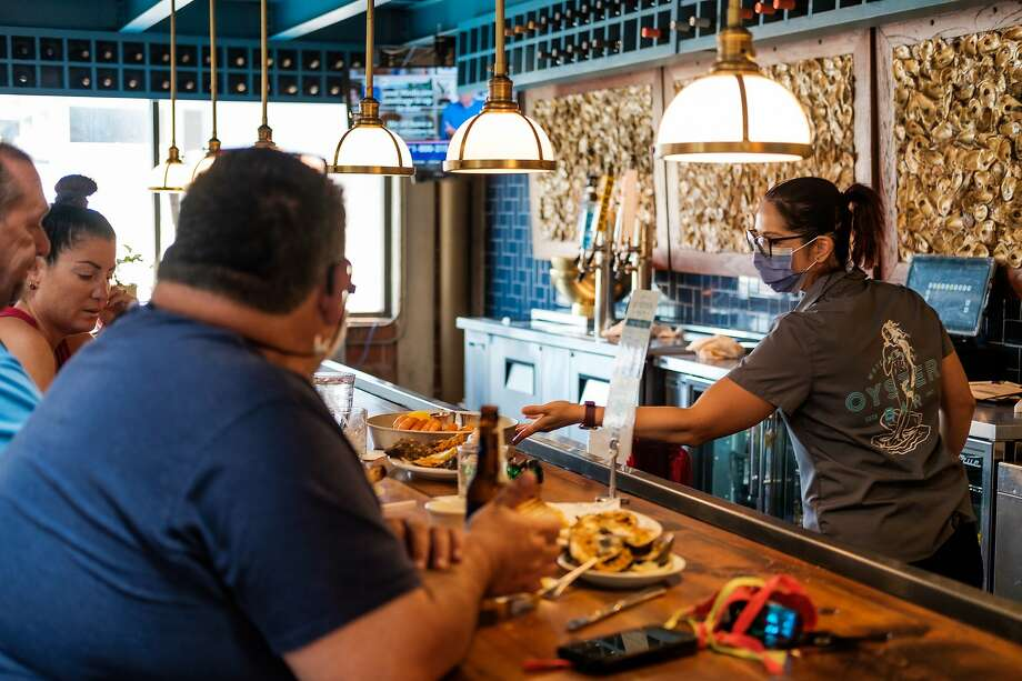 Brittany Thangiah works her shift at Water Street Oyster Bar in Corpus Christi on July 7. As of now, bars and other businesses will continue to remain open despite a surge in coronavirus cases. Photo: Christopher Lee, NYT