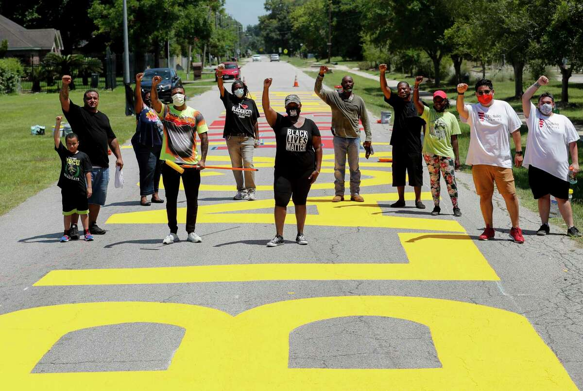 Members of the Acres Homes super neighborhood council pose for photograph as they painted a Black Lives Matter mural on Carver Road, just outside Carver High School on Saturday, July 11, 2020, in Acres Homes, Houston.