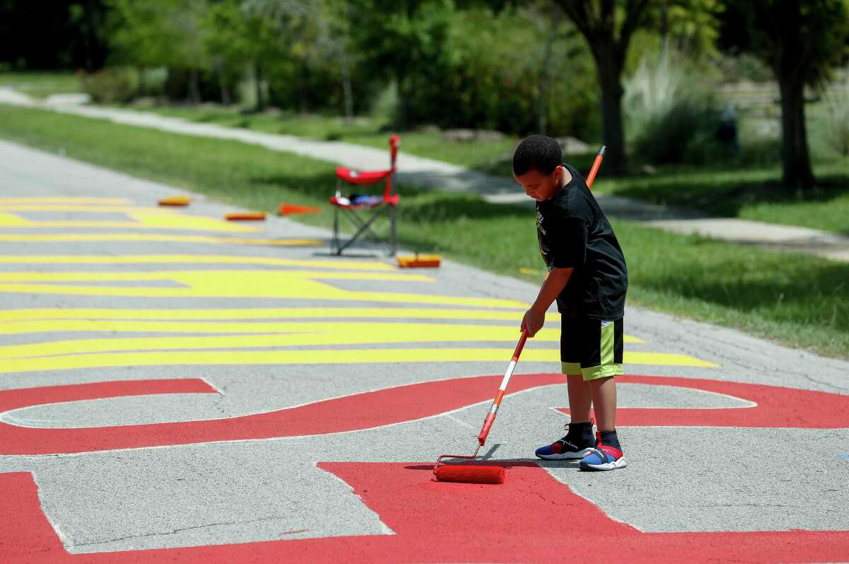 Major Thibodeaux, 7, helps paint a Black Lives Matter mural on Carver Road, just outside Carver High School on Saturday, July 11, 2020, in Acres Homes, Houston. The Acres Homes super neighborhood council organized the mural.