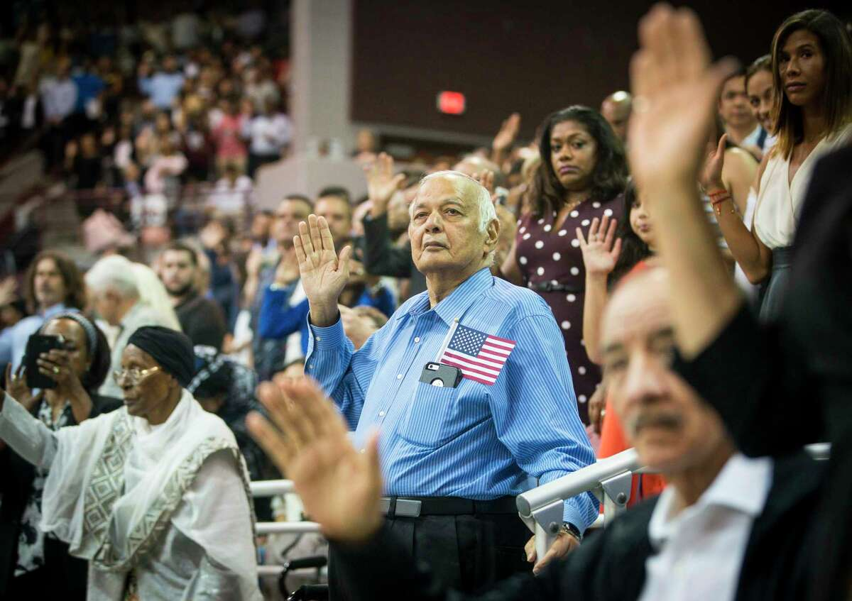 New citizens raise their hands to take the formal oath of allegiance to become naturalized United States citizens during a ceremony at the M.O. Campbell Education Center in Houston, Wednesday, July 10, 2019. 2,382 new citizens wore sworn in during the ceremony. The League of Women Voters registered 2,109 of the participants to vote.