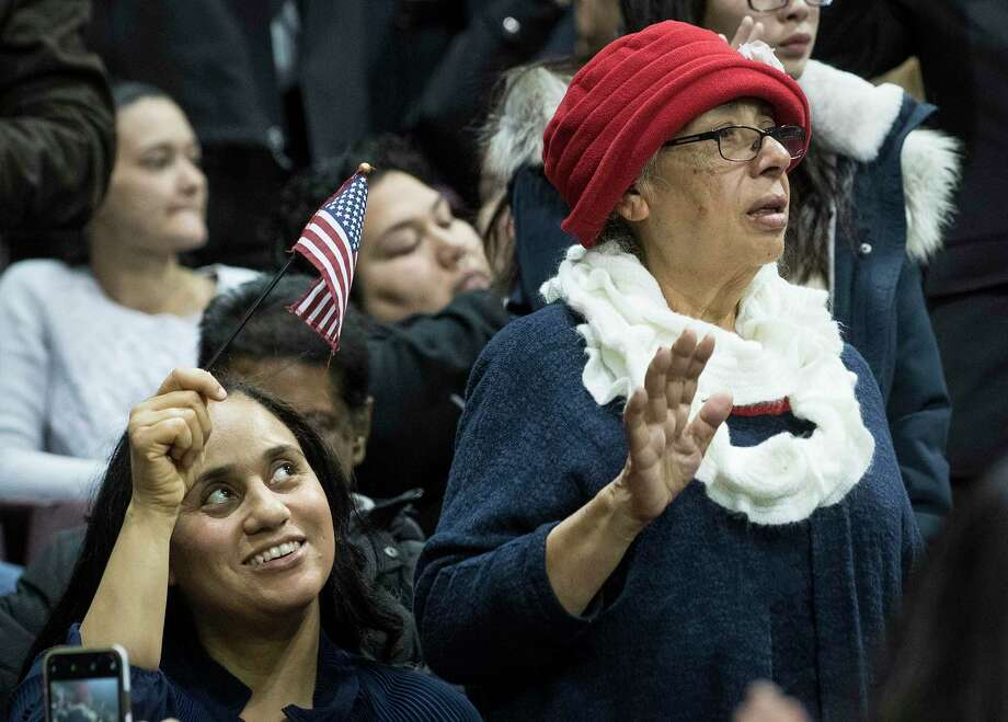 Shirley Smith, left, waves a flag as her mother, Aura Mireles, from Guatemala, takes the oath of allegiance during a naturalization ceremony for more than 2,500 new Americans at the M.O. Campbell Educational Center on Wednesday, Nov. 13, 2019, in Houston. As the state gears up for what could be its most important election in decades, thousands of would-be voters are caught in limbo, stuck in a deep and growing backlog of immigrants applying for U.S. citizenship. While the Trump administration says it is devoting resources to cut down on the backlog, and attorneys in Houston say immigrations officials do appear to be making an effort to get more applications through. Photo: Brett Coomer, Houston Chronicle / Staff Photographer / © 2019 Houston Chronicle