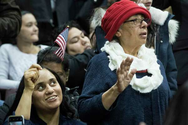 Shirley Smith, left, waves a flag as her mother, Aura Mireles, from Guatemala, takes the oath of allegiance during a naturalization ceremony for more than 2,500 new Americans at the M.O. Campbell Educational Center on Wednesday, Nov. 13, 2019, in Houston. As the state gears up for what could be its most important election in decades, thousands of would-be voters are caught in limbo, stuck in a deep and growing backlog of immigrants applying for U.S. citizenship. While the Trump administration says it is devoting resources to cut down on the backlog, and attorneys in Houston say immigrations officials do appear to be making an effort to get more applications through.
