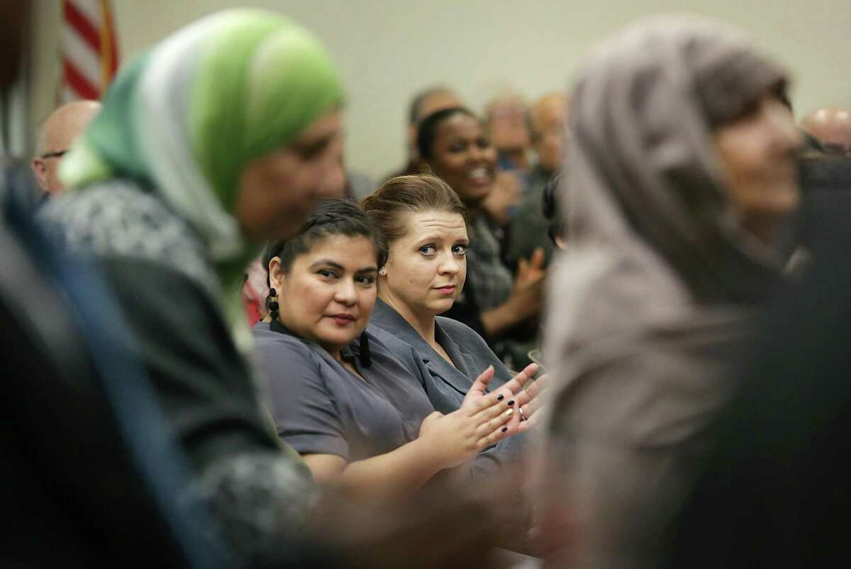 Alina Kaliuzhna, center right, watches immigrants stand as their birth country is called out during a naturalization ceremony.