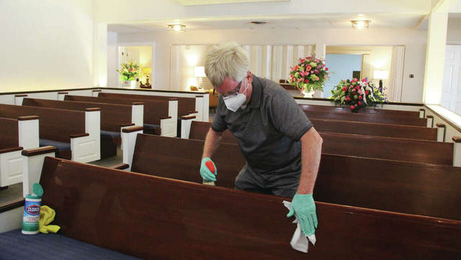 Custodian Larry Qualls cleans one of the pews Wednesday morning at Gent Funeral Home, in Alton. Concerns about COVID-19 have closed down funeral homes for some time, and now that they are reopening, additional cleaning and safety regulations are being put in place. Photo: Scott Cousins|The Telegraph