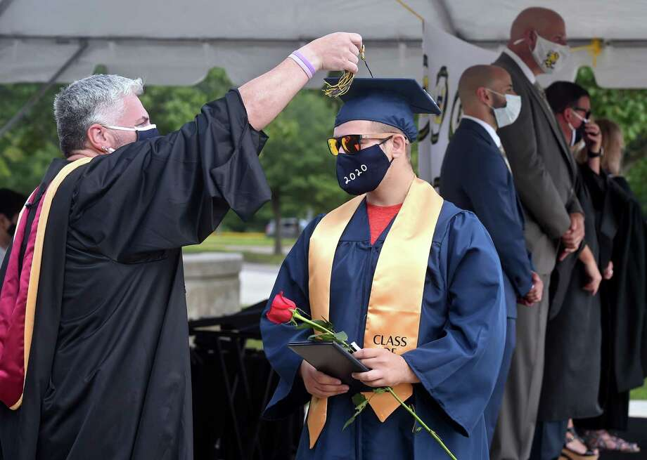 Vincenzo Bunce gets assistance with his tassel from Dean of Students Mark Hughes during the East Haven High School graduation ceremony in front of the school on July 11, 2020. Photo: Arnold Gold / Hearst Connecticut Media / New Haven Register
