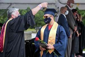 Vincenzo Bunce gets assistance with his tassel from Dean of Students Mark Hughes during the East Haven High School graduation ceremony in front of the school on July 11, 2020.