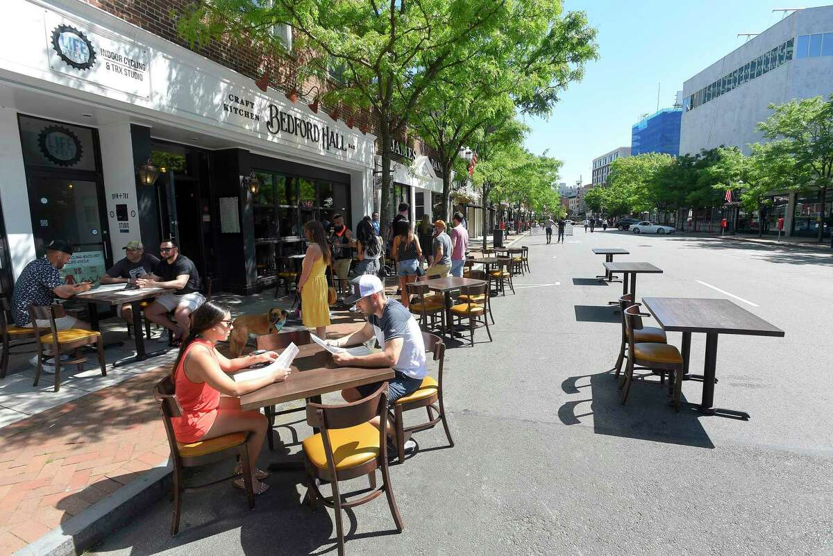 """Diners sit at tables outside Bedford Hall Craft Kitchen and Bar on May 30, 2020 in Stamford, Connecticut. """"A vaccine may not show up until the second quarter of 2021,"""" Director of Economic Development Thomas Madden said. """"The question is how we keep people in business until then."""""""