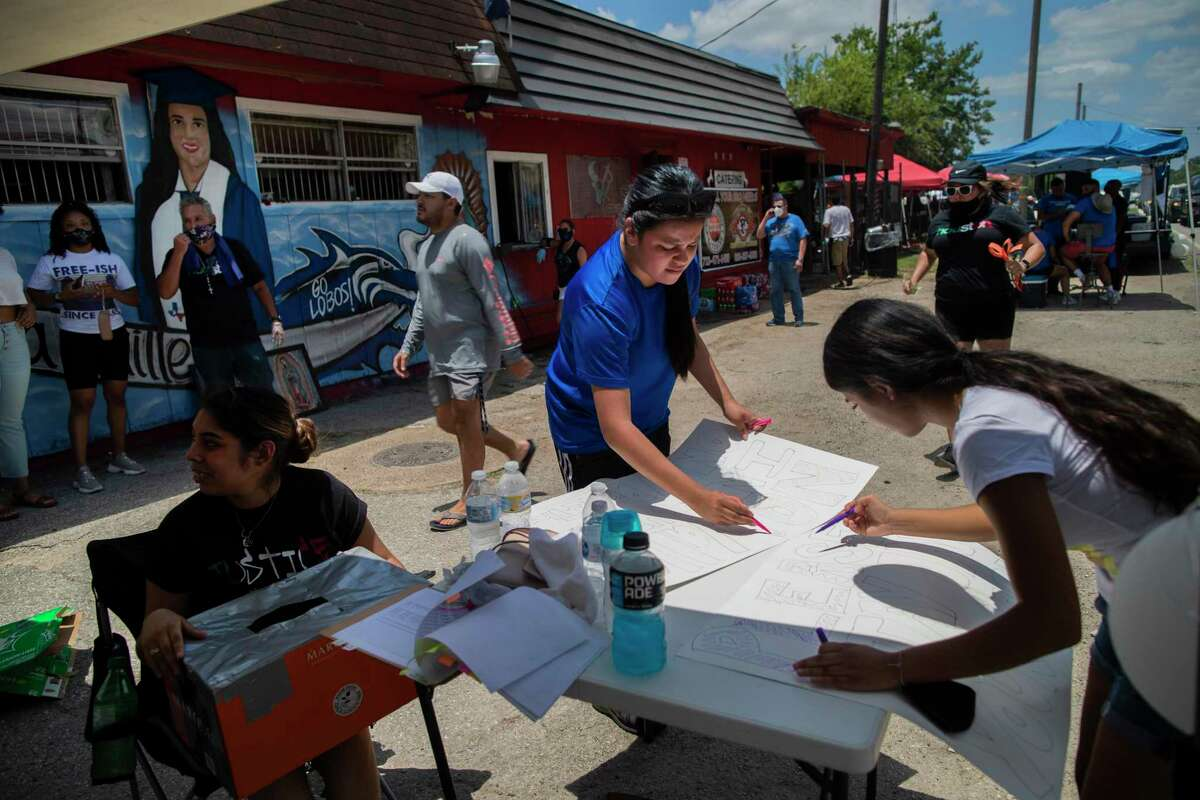 Lupe Guillén, center, 16, sister of Army Spec. Vanessa Guillén, prepares a sign during a BBQ fundraising event on Saturday, July 11, 2020, in Houston. The event is to raise funds to support the family of the soldier.