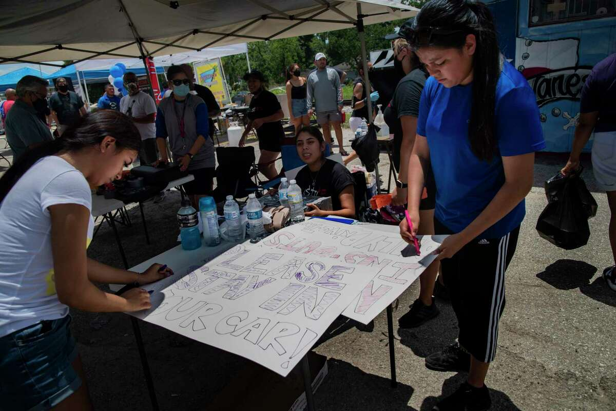 Lupe Guillén, right, 16, sister of Army Spec. Vanessa Guillén, and Cassandra Rangel, left,17, prepare a signs during a BBQ fundraising event on Saturday, July 11, 2020, in Houston. The event is to raise funds to support the family of the soldier.