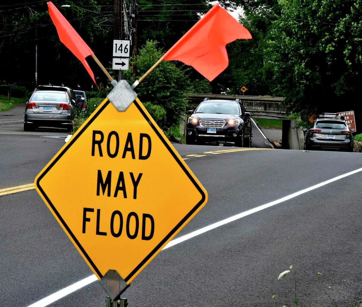 File photo showing a sign that warns motorists that Montowese Street near Pine Orchard Road in Branford, Conn., may flood underneath a railroad underpass.