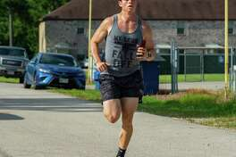 Nathan Benson runs in a sweat-soaked shirt in the Team 10k Run fundraiser for Pour Brothers Brewery at Crossfit Bridge City during the early morning heat on Saturday morning. Photo made on July 11, 2020. Fran Ruchalski/The Enterprise