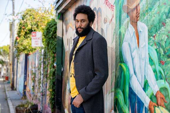 Poet, activist and San Francisco native Tongo Eisen-Martin poses for a portrait in front of a mural painted by his godmother Miranda Bergman along Balmy Alley in the southern Mission District of San Francisco, Calif. Friday, July 10, 2020. Eisen-Martin is an award-winning poet and political educator who has taught at Rikers Island and San Quentin with work surrounding Bay Area gentrification.