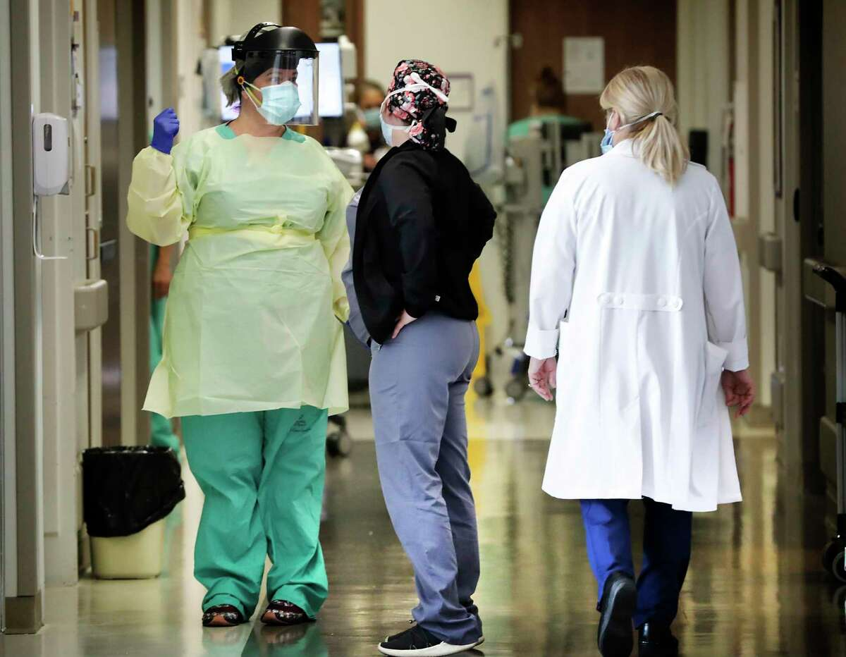 Irene Martin, left, confers with another nurse before entering a patient's room at University Hospital on July 8, 2020. More space, resources and staff have been reallocated to handle the rapidly rising number of COVID-19 patients since June.