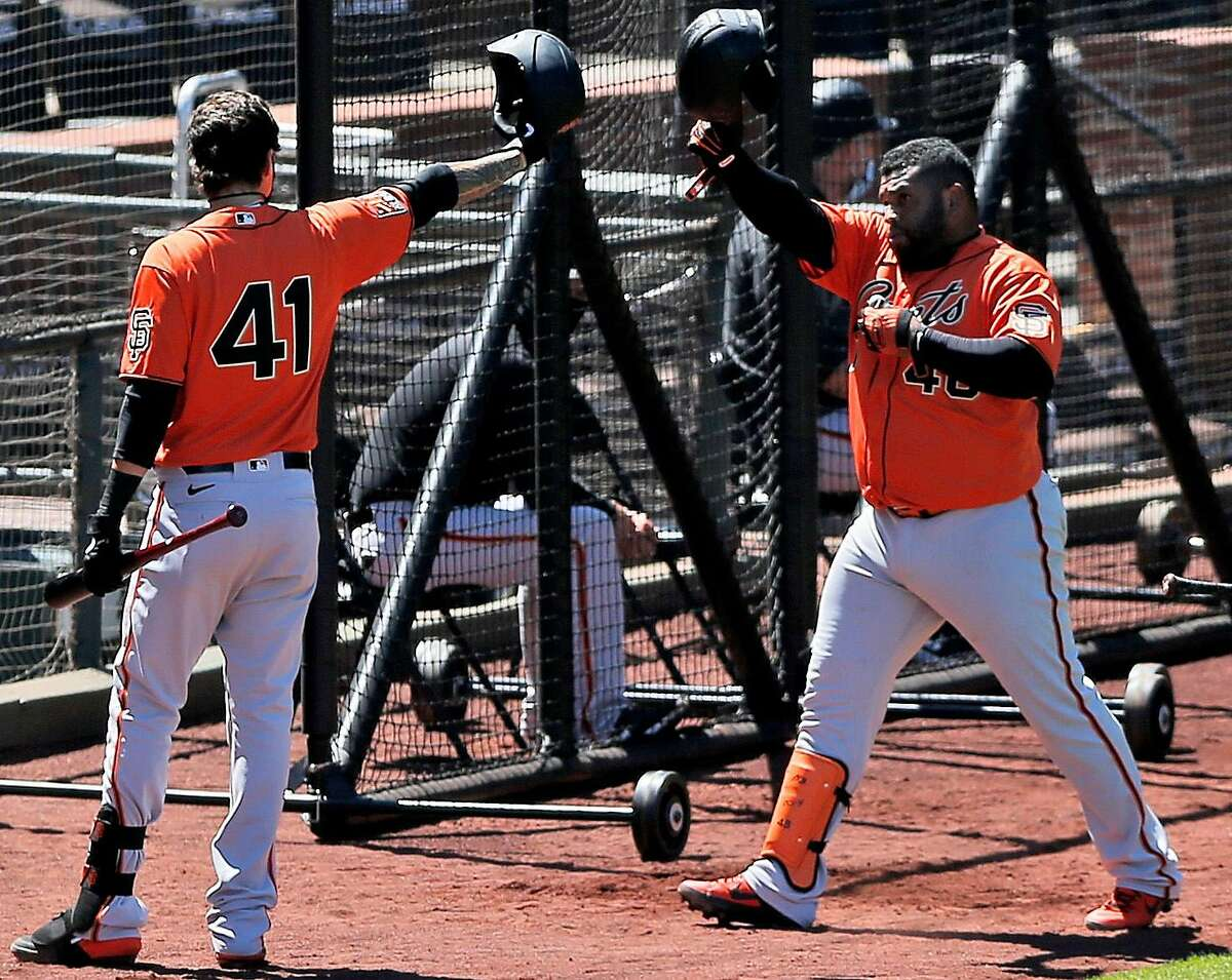 San Francisco Giants Pablo Sandoval (center) bumps helmets with Giants Wilmer Flores after Sandoval scored a two-run homer in a simulated game during Spring Training at Oracle Park on Saturday, July 11, 2020, in San Francisco, Calif. He air-fived his teammates in the dugout, amid the coronavirus pandemic.