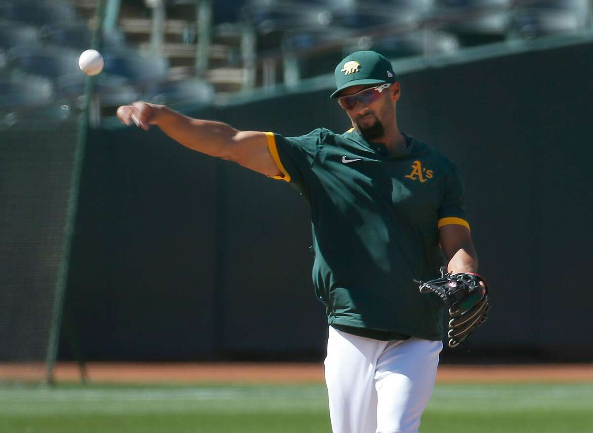 Marcus Semien throws to first base during the Oakland A's summer training camp at the Coliseum in Oakland, Calif. on Saturday, July 11, 2020.