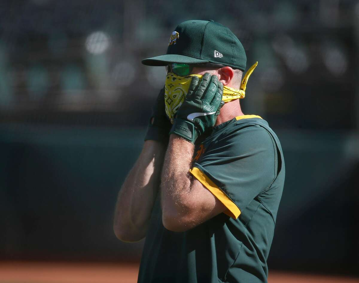 Bench coach Ryan Christenson adjusts his face covering during the Oakland A's summer training camp at the Coliseum in Oakland, Calif. on Saturday, July 11, 2020.